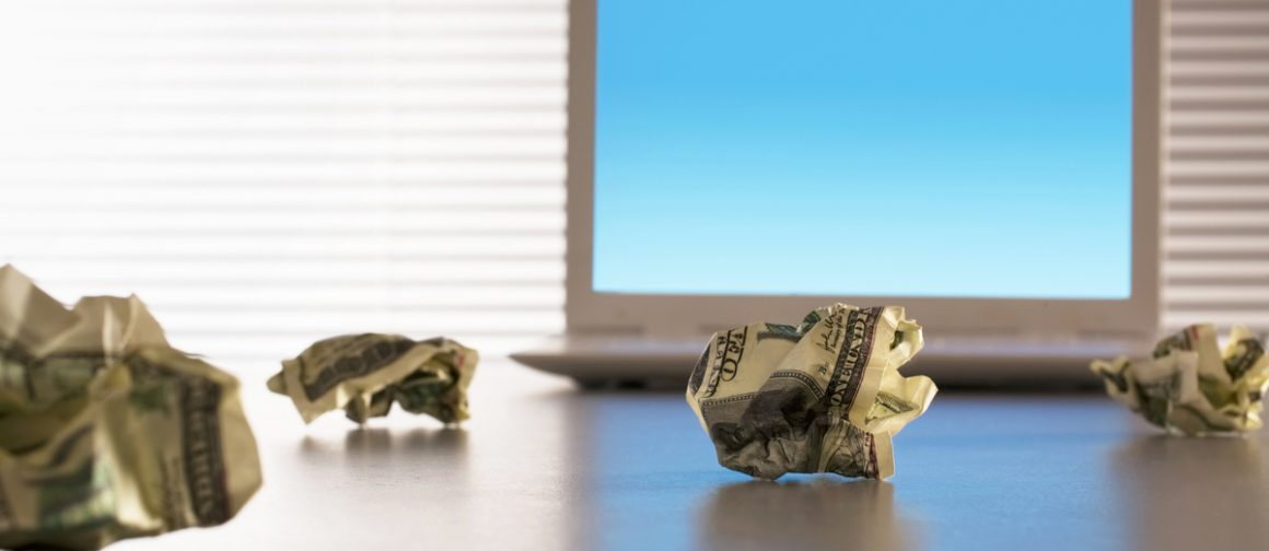 crumpled up dollar bills on desk with laptop