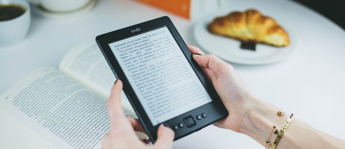 woman reading a book on Kindle