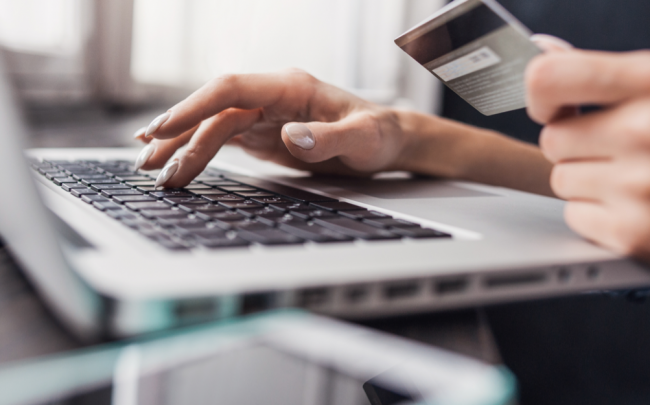 woman online shopping with credit card in hand