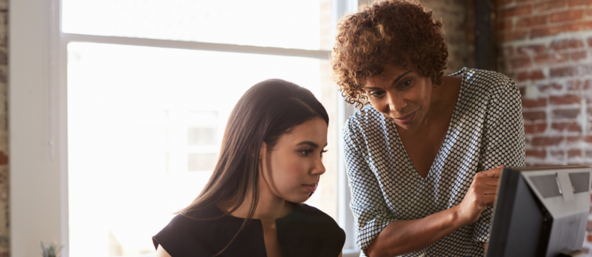 women work together at computer